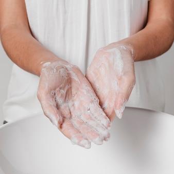 Strofinando le mani con acqua e sapone vista frontale
