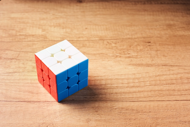 Rubics cube on a wooden background, top view