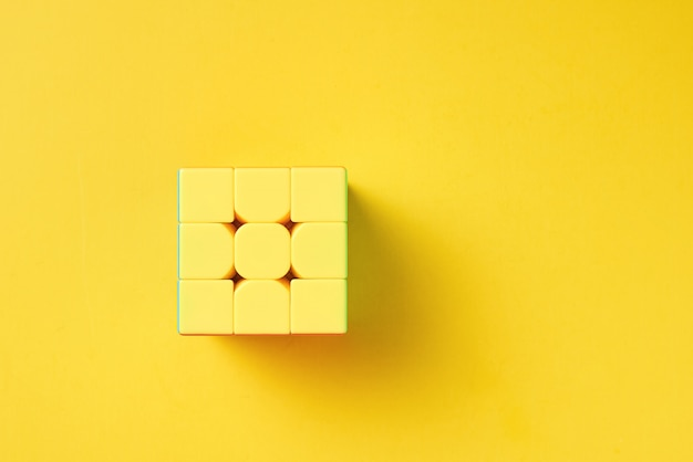 Rubics cube on a yellow background, top view