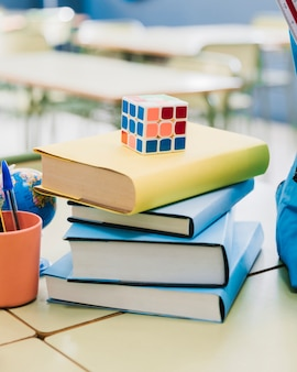 Rubik cube placed on stacked books on desk in classroom