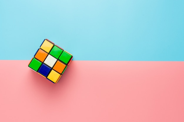 Rubik's cube on pink and blue background.