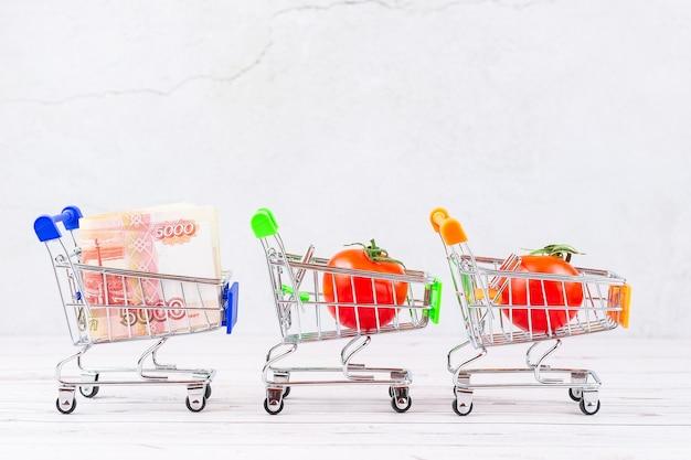 Рублевые купюры перемешались в корзине рядом с корзиной, полной красных спелых помидоров