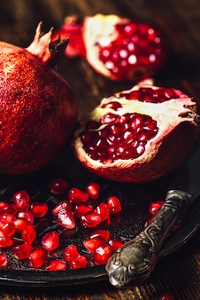 Ruby pomegranate with seeds and knife.