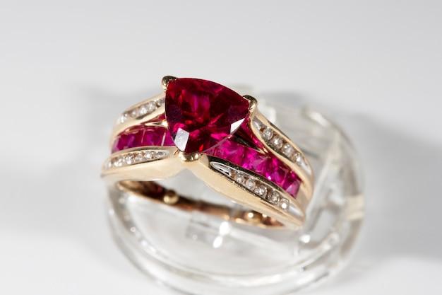 다이아몬드로 둘러싸인 루비 링, 트릴리온 컷, 스탠드 위의 옐로우 골드 링