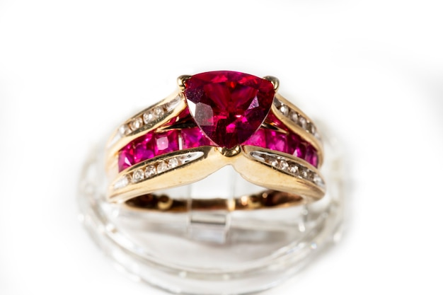 Ruby ring surrounded by diamonds,trillion cut, yellow gold ring on a stand