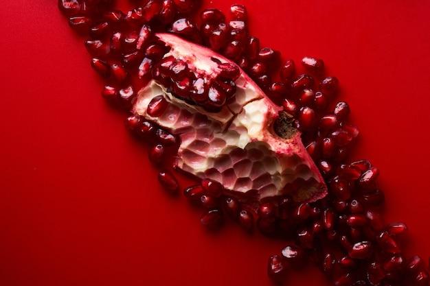 붉은 배경에 분리된 루비 잘 익은 신선한 즙이 많은 얇게 썬 석류