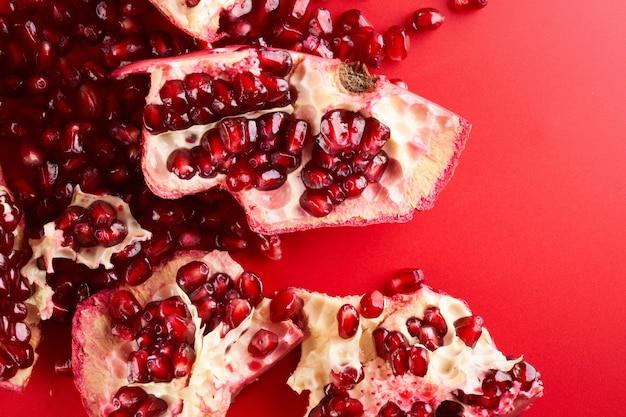 붉은 배경에 격리된 루비 잘 익은 신선한 육즙 얇게 썬 석류