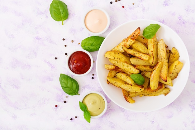 Ruddy baked potato wedges with herbs on a light background.