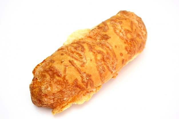 The ruddy long loaf of bread is strewed by cheese isolated