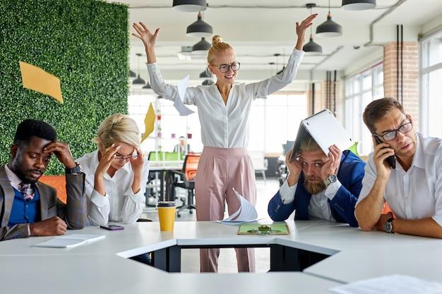 무례한 화난 여성 상사 임원은 직원들에게 불만을 품고 비명을 지른다.