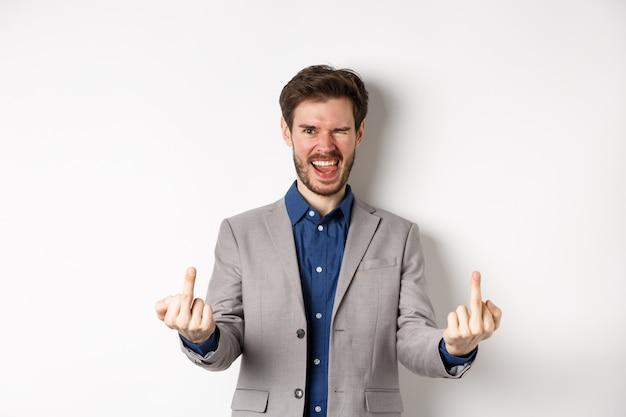 Rude ignorant guy in business suit showing middle fingers and tongue, smiling while mocking people, fuck you gesture, standing on white background.
