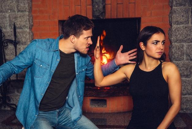 Грубый молодой человек сердится на молодую женщину. он машет левой рукой. модель показывает стоп-вздох. она не хочет его слушать. они сидят у камина