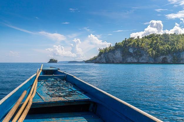 小さな島の前の海の真ん中にある初歩的な青いボート、旅行のコンセプト
