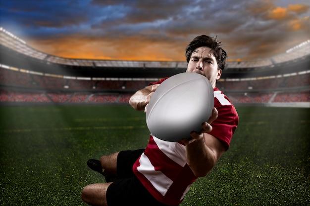 赤いユニフォームを着たラグビー選手。