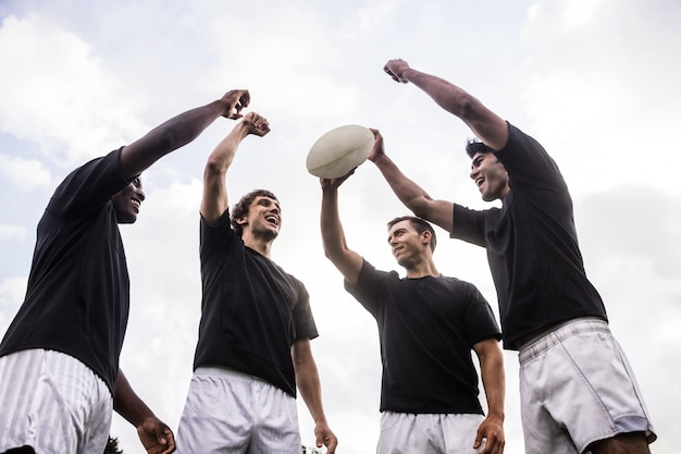 Rugby players cheering together with ball