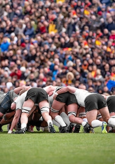 Rugby team in a team hug with blurred spectators