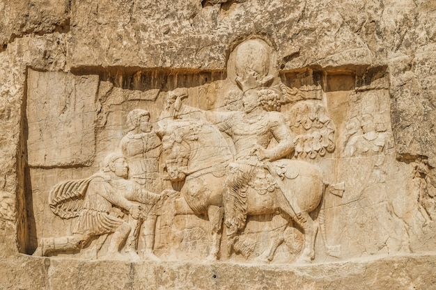 A ruin and ancient sassanid rock relief depiction at naqsh-e rostam, iran.