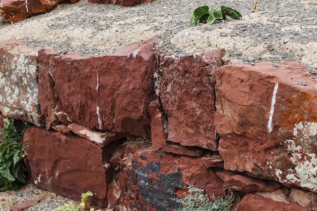 アクルタスパレスコンプレックスの廃墟の古代の壁。カザフスタン。赤い砂岩の壁。