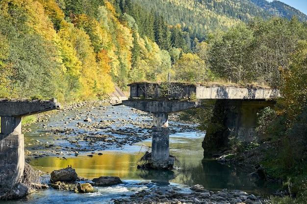 Разрушенный мост на горной реке. руины колонн моста в карпатах.