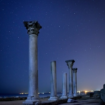 Ruins of ancient city columns under blue night sky with moon and stars