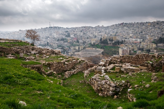 The ruins of the citadel over the city of amman and and roman theater jordan on a spring cloudy day