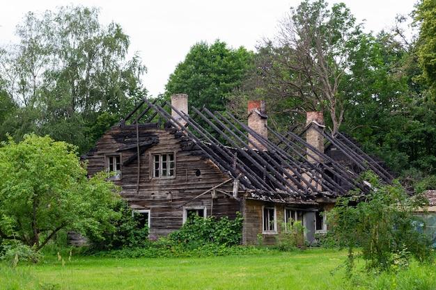周りに屋根のない緑の夏の庭のない古い木造の焼失した家の廃墟