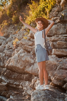 彼女の手で帽子とrukzakの流行に敏感な若い女性