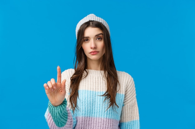 Rule number one. serious-looking assertive woman in winter sweater, hat, raising one finger in disapproval, restriction or warning, prohibit do something, not so fast gesture, blue wall