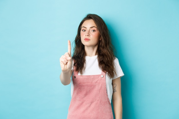 ルールナンバーワン。不承認で指を振る、悪い決定を叱る、青い背景に立って、ブロックまたはタブーのジェスチャーをする深刻な若い美しい少女。