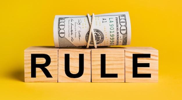 黄色の背景にお金のルール。ビジネス、金融、クレジット、収入、貯蓄、投資、交換、税金の概念