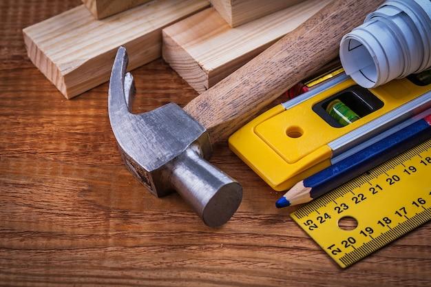 定規鉛筆の青写真は、ヴィンテージの木板のメンテナンスコンセプトに木製のレンガの建設レベルとクローハンマーを描きます。 Premium写真