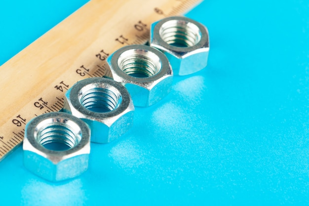 Ruler and various nuts on  blue surface