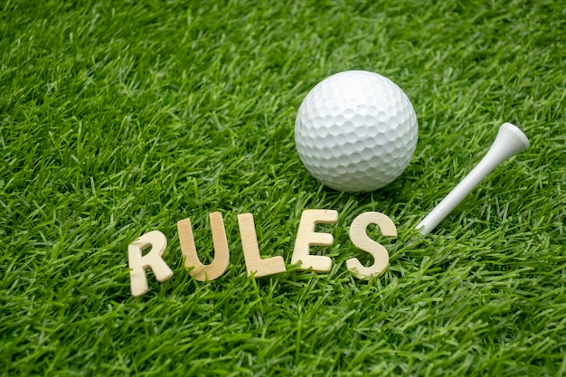 The rules of golf concept with golf ball and word of rules are on green grass.
