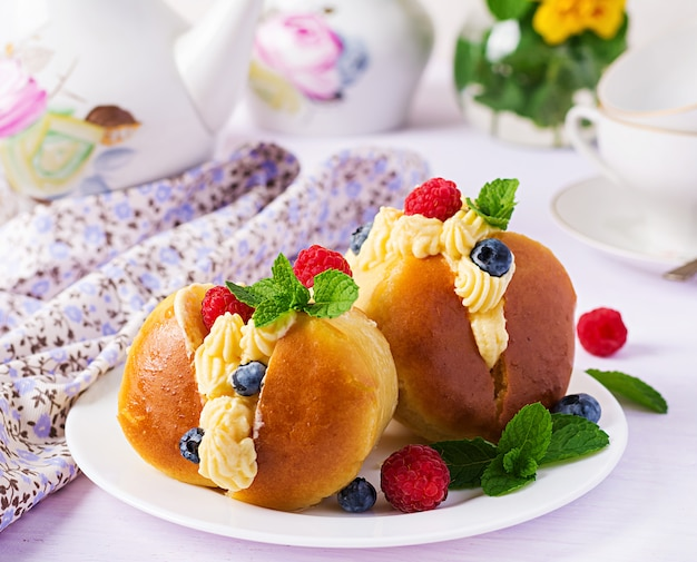 Rum baba decorated with whipped cream and fresh raspberry, blueberry. savarin with rum, cream and berries.