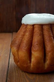 나무 배경에 럼 바바입니다. 케이크는 보통 럼주에 담근 독주로, 때로는 휘핑 크림이나 페이스트리 크림으로 채워집니다.