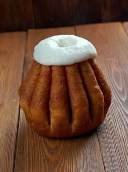 나무 표면에 럼 바바. 보통 럼주와 같은 단단한 주류에 포화 된 케이크, 때로는 휘핑 크림 또는 페이스트리 크림으로 채워집니다.