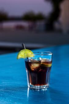 Ром-кола повседневный коктейль с кубиками льда и лаймом на фоне летней стойки бара