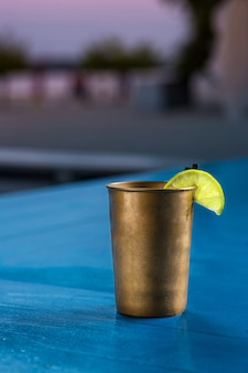 Rum cola casual cocktail with ice cubes and lime at summer bar stand background