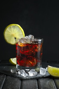Rum and cola cocktail on dark