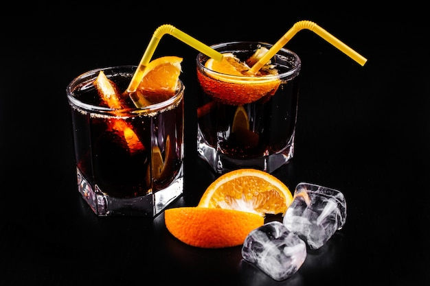 Rum and cola refreshing alcohol cocktail drink in highball glass with orange and ice
