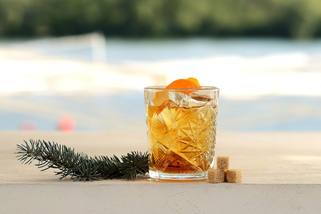 Rum in a glass with ice and orange peel