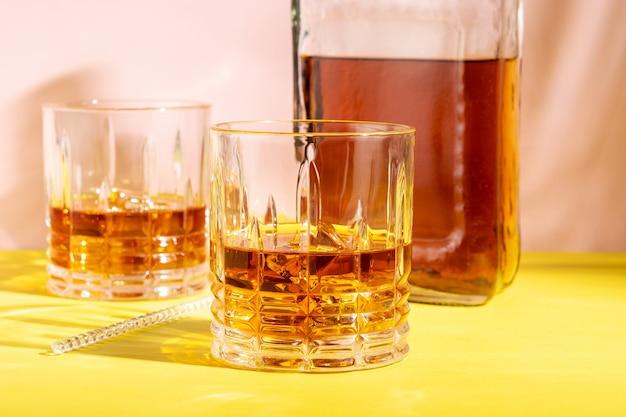 明るい背景のグラスに氷を入れたラム酒またはアマレットサワー。