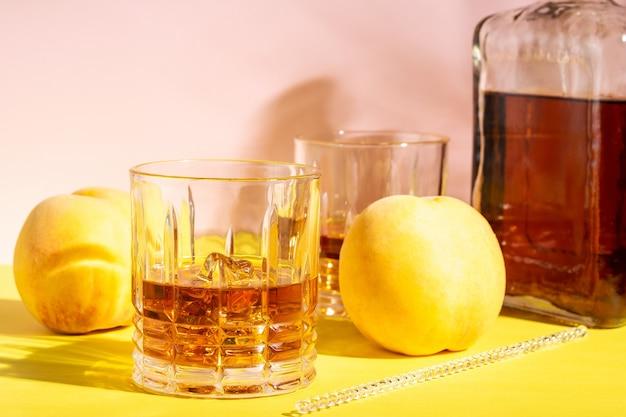 Ром или амаретто кислый со льдом в стакане на ярком фоне.