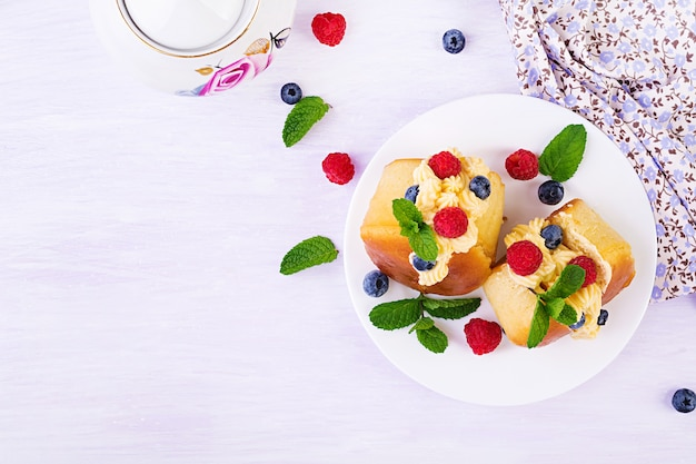 Rum savarian buns decorated with whipped cream and fresh berries