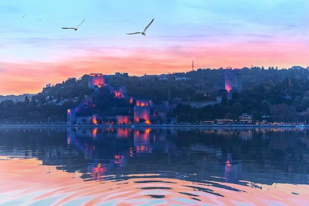 Замок румелиан в цветах заката и вечерних огнях, стамбул.