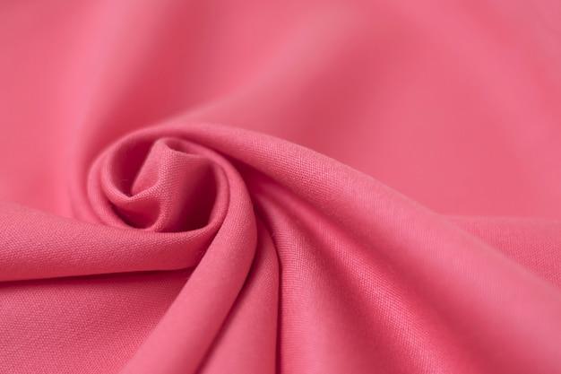 Помятая розовая текстура ткани. мягкий фокус