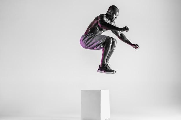 感情のために走りなさい。灰色のスタジオの背景の上に若いアフリカ系アメリカ人のボディービルダーのトレーニング。スポーツウェアでジャンプする筋肉の単一の男性モデル。スポーツ、ボディービル、健康的なライフスタイルの概念。