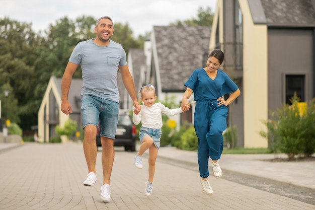 Run and fun. daughter wearing denim skirt running while having fun with parents