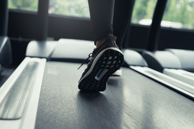 Run. motion runner woman feet running on machine treadmill at fitness gym center or health club with sunlight effect