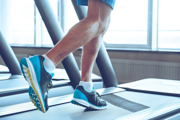 Run to success. close-up part of man in sports shoes running on treadmill at gym
